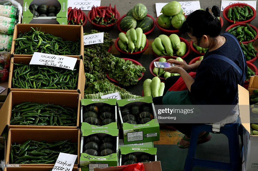A vegetable vendor plays a game on her smartphone at Samsan Agricultural Wholesale Market in Incheon, South Korea, on Friday, Aug. 16, 2013. South Korean producer prices declined 0.9 percent in July from a year earlier after a 1.4 percent drop in June, the central bank said in a statement today. Photographer: SeongJoon Cho/Bloomberg via Getty Images