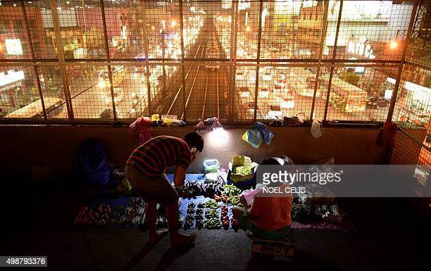 A vegetable vendor talks to a customer on an overpass in Manila on November 26 2015 The Philippine economy grew slower than expected in the third...