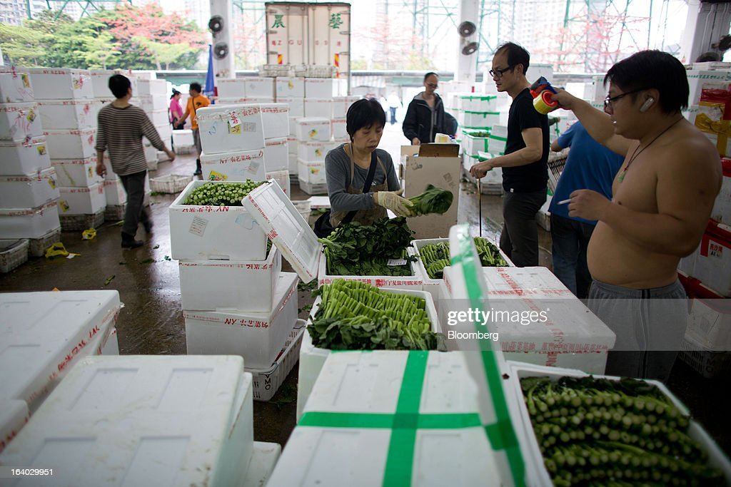 A vegetable wholesaler handles choi sum at the Cheung Sha Wan Wholesale Vegetable Market in Hong Kong, China, on Tuesday, March 19, 2013. Hong Kong's economy expanded 1.4 percent in 2012 and Financial Secretary John Tsang is projecting growth of 1.5 percent to 3.5 percent this year. Photographer: Lam Yik Fei/Bloomberg via Getty Images