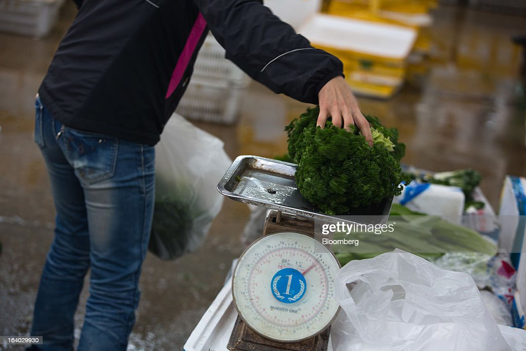A vegetable wholesaler weighs parsley at the Cheung Sha Wan Wholesale Vegetable Market in Hong Kong, China, on Tuesday, March 19, 2013. Hong Kong's economy expanded 1.4 percent in 2012 and Financial Secretary John Tsang is projecting growth of 1.5 percent to 3.5 percent this year. Photographer: Lam Yik Fei/Bloomberg via Getty Images