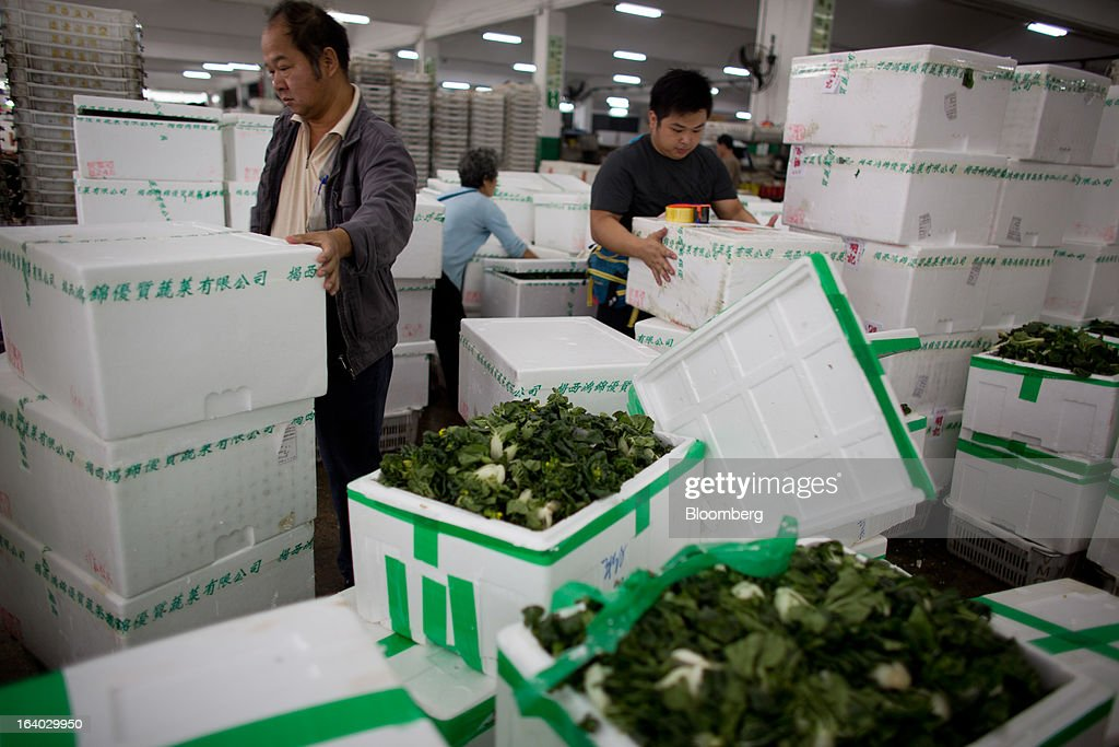 Vegetable wholesalers handle sealed foam boxes behind open boxes of baby bok choy at the Cheung Sha Wan Wholesale Vegetable Market in Hong Kong, China, on Tuesday, March 19, 2013. Hong Kong's economy expanded 1.4 percent in 2012 and Financial Secretary John Tsang is projecting growth of 1.5 percent to 3.5 percent this year. Photographer: Lam Yik Fei/Bloomberg via Getty Images.