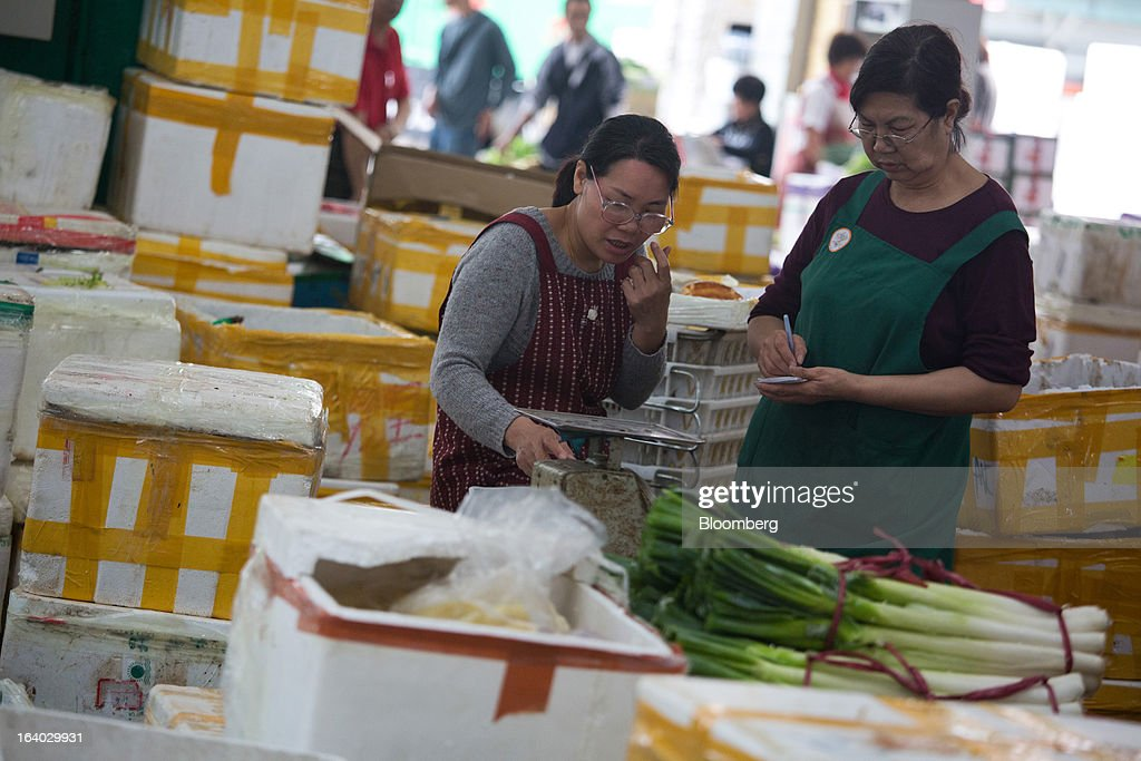 Vegetable wholesalers work behind a bundle of leeks at the Cheung Sha Wan Wholesale Vegetable Market in Hong Kong, China, on Tuesday, March 19, 2013. Hong Kong's economy expanded 1.4 percent in 2012 and Financial Secretary John Tsang is projecting growth of 1.5 percent to 3.5 percent this year. Photographer: Lam Yik Fei/Bloomberg via Getty Images