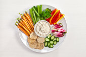 Vegetables and dip plate on white table shot from above