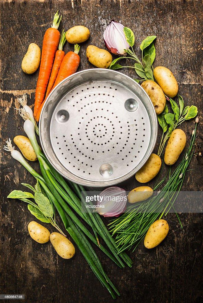 vegetables around empty colander bowl on dark rustic wooden background : Stock Photo