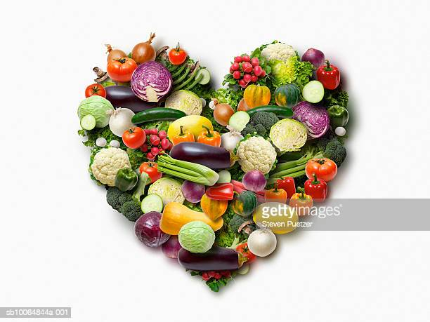 Vegetables arranged in heart shape on white background (Digital Composite)