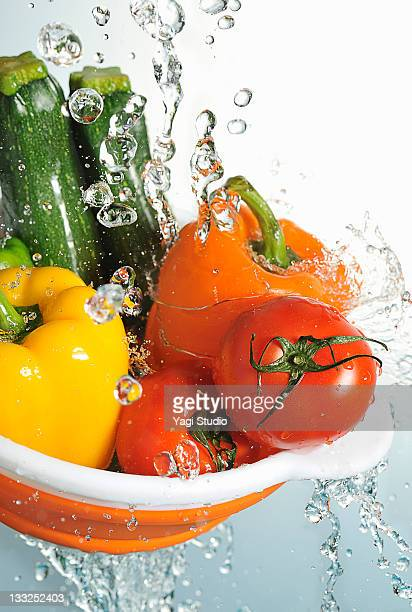 Vegetables in a orange colander,and water