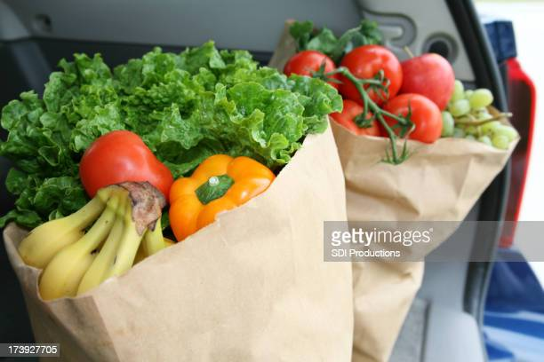 Vegetables In Bags Sitting The Trunk Of A Car