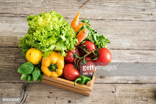 Vegetables in basket on wooden table : Stock Photo