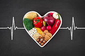 Heart health concept with related foods in white heart shaped bowl. potato red peppers, broccoli, radish, red onion, garlic, dry beans, almonds, nuts, and other legumes were arranged in heart shape pl