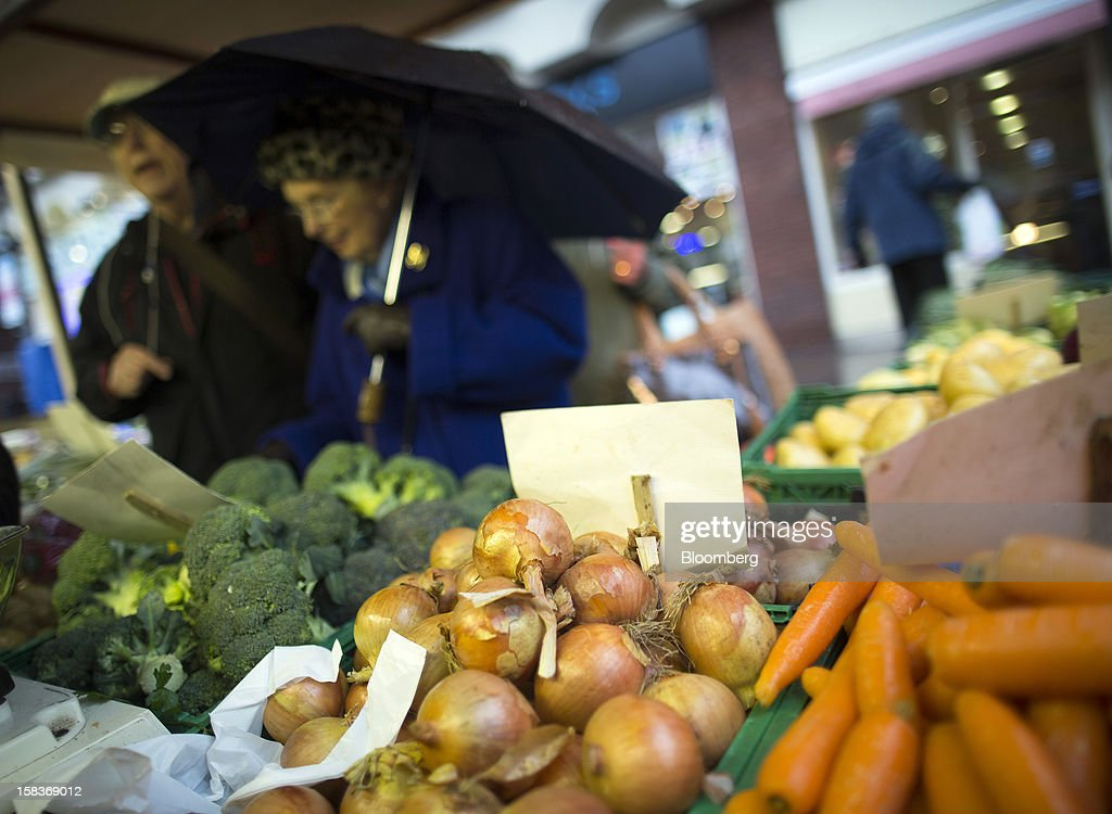 Vegetables, including broccoli, white onions and carrots, are displayed for sale on a fruit and vegetable stall at a market in Guildford, U.K., on Friday, Dec. 14, 2012. Standard & Poor's lowered its outlook on Britain's top credit rating to negative, citing weak economic growth and a worsening debt profile. Photographer: Simon Dawson/Bloomberg via Getty Images