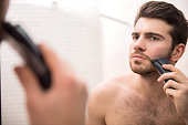 Handsome young man is shaving with electric razor while looking at the mirror.Young handsome man holds pepper, isolated on white background.