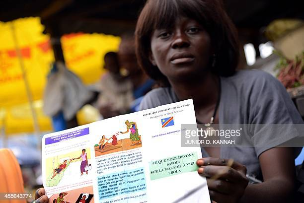 A vegetable's seller holds a Congolese Ministry of Health's information leaflet on Ebola virus on September 17 2014 on Moral's market in the Bandal...