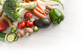 vegetables such as broccoli, carrots, peppers, mushrooms, tomatoes, green onions, avocado, brussels sprouts on white wood, corner background fades to white, concept of healthy food and slimming low ca