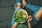 Green vegan breakfast meal in bowl with spinach, arugula, avocado, seeds and sprouts. Girl in jeans holding fork with knees and hands visible, top view, copy space. Clean eating, vegan food concept