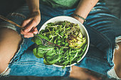 Green vegan breakfast meal in bowl with spinach, arugula, avocado, seeds and sprouts. Girl in jeans holding fork with knees and hands visible, top view. Clean eating, dieting, dieting food concept