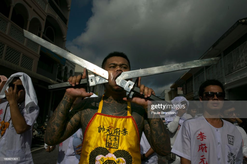 Vegetarian festival devotees parade through the streets of downtown Phuket, Thailand on October 10, 2013. Ritual Vegetarianism in Phuket Island traces it roots back to the early 1800's. The festival begins on the first evening of the ninth lunar month and lasts for nine days. Participants in the festival perform acts of body piercing as a means of shifting evil spirits from individuals onto themselves and bring the community good luck.
