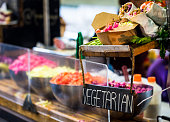 Close up image of a selection of vegetarian food for sale on a market stall at the famous Borough Market in London, UK. One of the main items for sale is vegetarian wraps, and we can see big bowls of