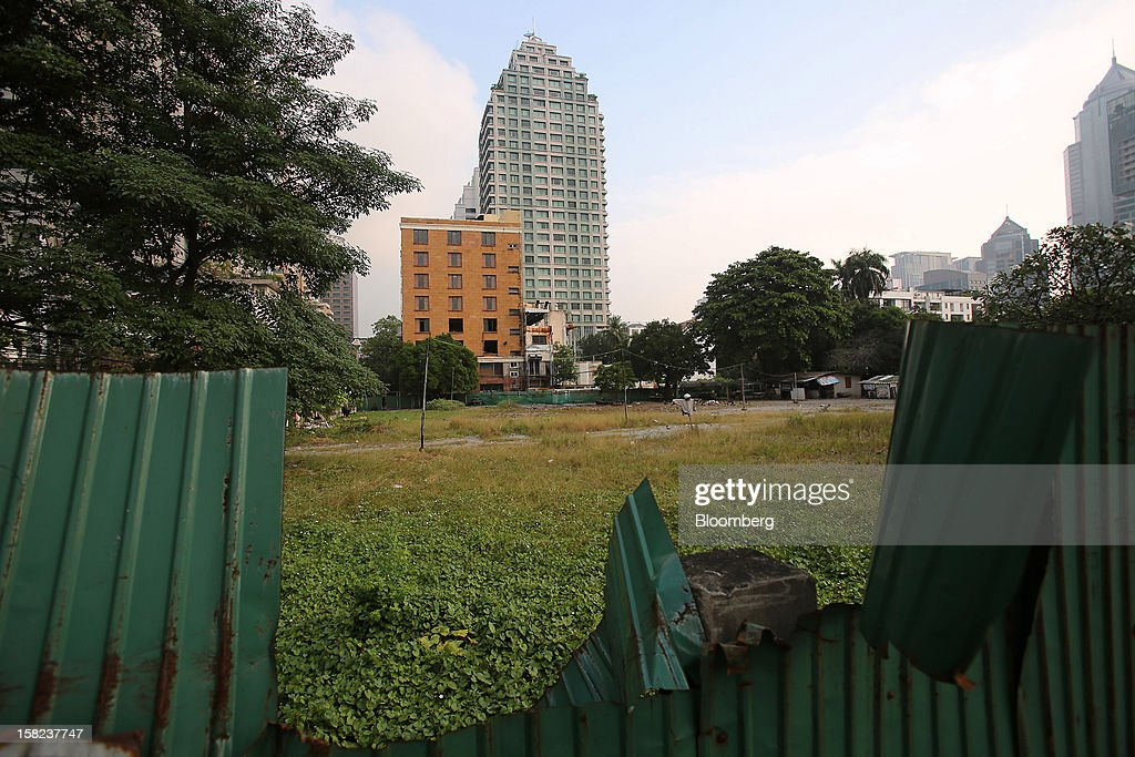 Vegetation grows on a plot of land along Langsuan road as high rise buildings stand in the background in Bangkok, Thailand, on Tuesday, Dec. 11, 2012. The Crown Property Bureau owns about 41,300 rai (66 square kilometers) of land across the country, about a fifth of which is in Bangkok, according to Aviruth Wongbuddhapitak, an adviser to the CPB who sits on the board of two of its subsidiaries. Photographer: Dario Pignatelli/Bloomberg via Getty Images