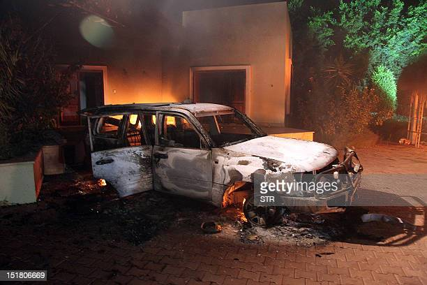 A vehicle and surrounding buildings smolder after they were set on fire inside the US consulate compound in Benghazi late on September 11 2012 An...