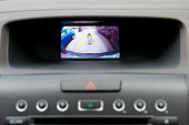 A car back up camera video diplay in the automobile dashboard showing a wide angle view of what's behind the car.  In this case, there is a child directly behind the car and another vehicle beside the