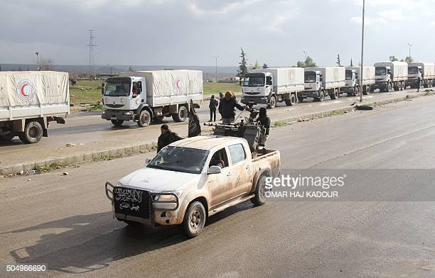 TOPSHOT A vehicle belonging to Jaish alFatah drives along convoys from the Syrian Arab Red Crescent carrying aid for the besieged towns of Fuaa and...