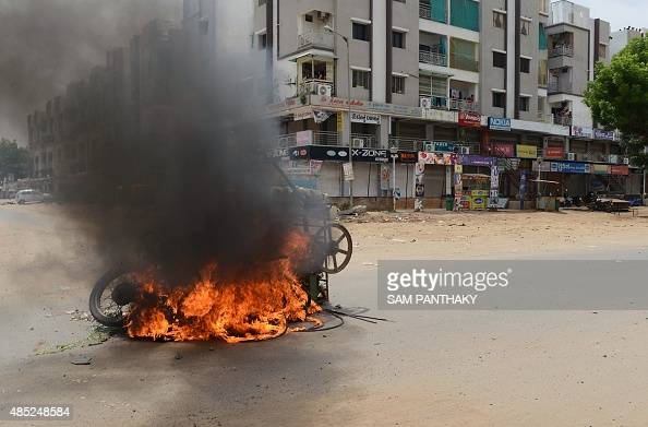 A vehicle burns after riots on a street in Ahmedabad on August 26 2015 Thousands of Indian paramilitary troops have been sent to the western state of...