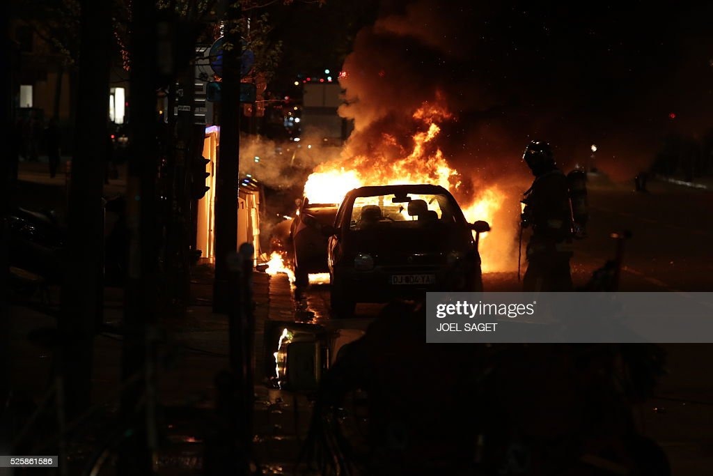 A vehicle burns as French Gendarmerie clear the Place de la Republique during a protest by the Nuit Debout, or 'Up All Night' movement who have been rallying against the French government's proposed labour reforms early on April 29, 2016. Twenty-seven people were arrested and 24 detained during the overnight clashes in the French capital as the police dispersed the protesters who began their began movement on March 31 in opposition to the government's proposed labour reforms.