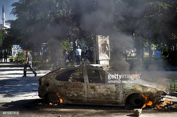 A vehicle burns during clashes between riotpolice and protesters on June 22 2014 in the divided town of Mitrovica Kosovo police used tear gas today...
