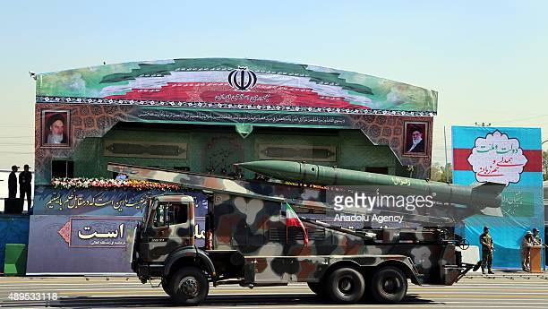 A vehicle carrying a missile system is driven past Iranian military commanders during the annual military parade marking the anniversary of the start...