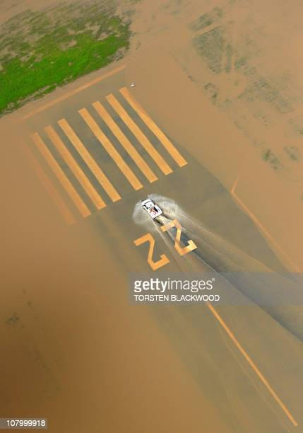 A vehicle drives down the flooded runway at Rockhampton Airport on January 5 2011 after the swollen Fitzroy River broke its banks and inundated much...