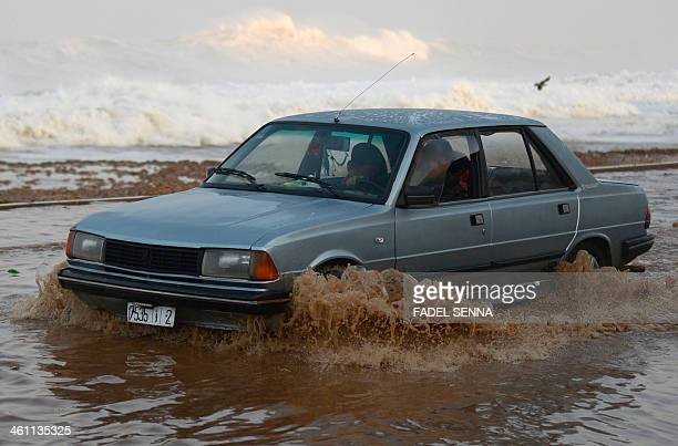 A vehicle drives in sea water and past rocks and debris after huge waves crashed along the Atlantic costal road in the Moroccan city of Rabat during...