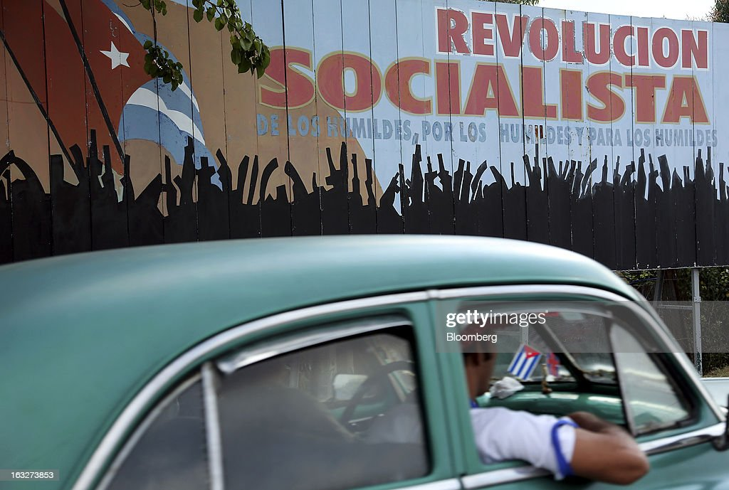 A vehicle drives past a billboard saluting socialist revolution in Havana, Cuba, on Wednesday, March 6, 2013. Cuba's government praised Venezuelan President Hugo Chavez following his death yesterday for uniting the people of Latin America and pledged loyalty to the continuation of his Bolivarian Revolution, according to the statement in the state-run Granma website. Photographer: Noah Friedman-Rudovsky/Bloomberg via Getty Images