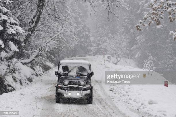 A vehicle drives past a snowcovered Gulmarg Tangmarg road on December 11 2017 about 38 kilometers from Srinagar India