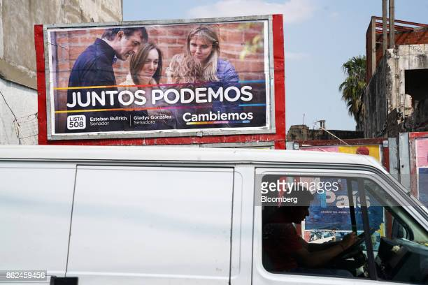 A vehicle drives past campaign posters for candidate Esteban Bullrich displayed on a wall in the Hurlingham neighborhood of Buenos Aires Argentina on...