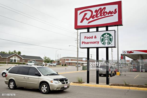 A vehicle drives past signage for a Dillons Food Stores supermarket owned by Kroger Co in Hays Kansas US on Thursday June 29 2017 Kroger remains...