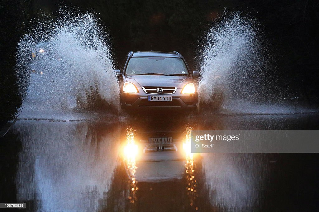 A vehicle drives through flood waters from the River Thames on December 29, 2012 in Sonning, England. The Environment Agency has issued widespread flood warnings across the UK whilst the Met Office has predicted further rain forecast for the remainder of 2012, which is likely to be recorded as the wettest year since records began in 1910.