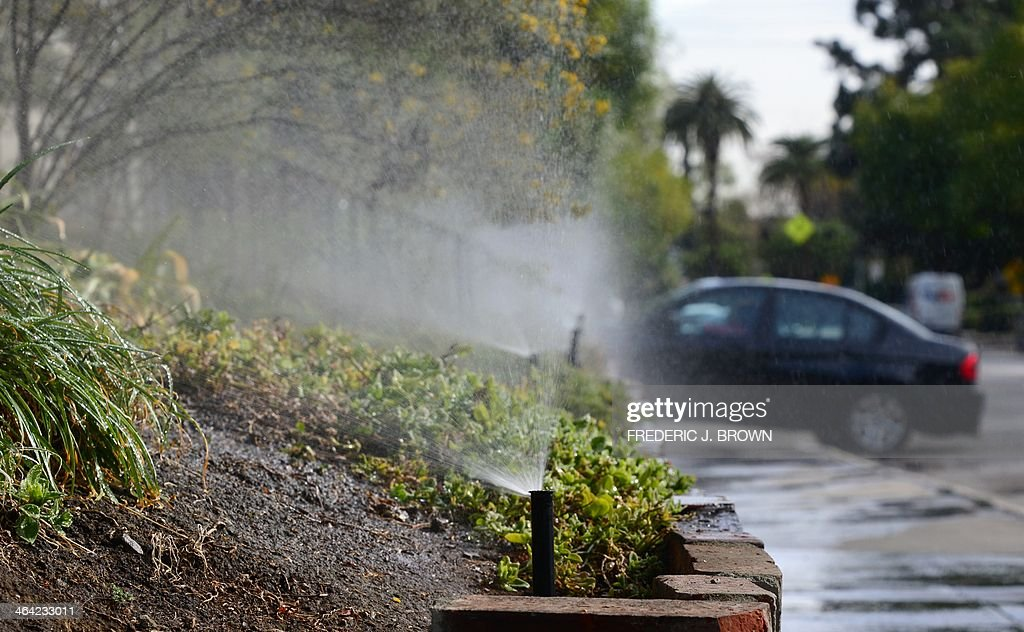 A vehicle enters a driveway at the end of a row of sprinklers watering plants and foliage in front of an apartment complex in South Pasadena...
