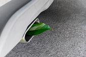 Fuel efficient car muffler with a green leaf.