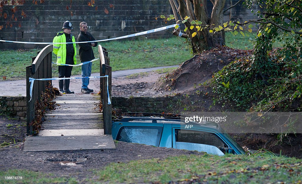 A vehicle in which a man died after being trapped in flood waters is wedged under a bridge following heavy rainfall in Chew Stoke, Somerset, southwest England, on November 23, 2012. Swathes of Britain were hit by by heavy rains and strong winds for a second day on Thursday, with authorities warning of worse flooding to come at the weekend. AFP PHOTO/WILL OLIVER