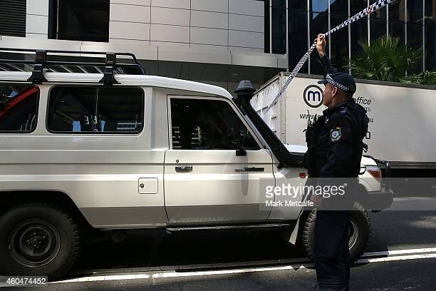 A vehicle is allowed through a police barricade on Phillip St on December 15 2014 in Sydney Australia Police attend a hostage situation at Lindt Cafe...