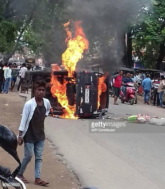 A vehicle is seen in flames along a road after a man was lynched by a mob on the suspicion of carrying beef meat in his car in Ramgarh district of...