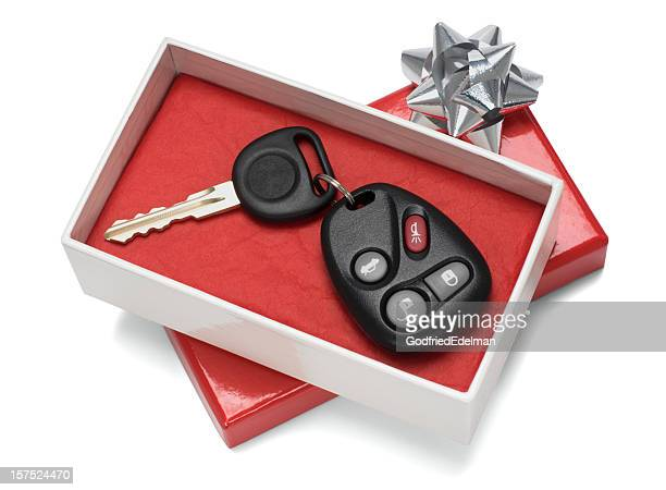 Vehicle keys in white and red gift box with silver bow