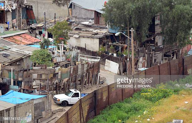A vehicle makes its way along an alley in a Tijuana Mexico neighborhood where residents literally live across the fence from the United States living...