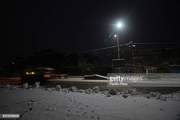 A vehicle moves early morning after the fresh snowfall in Srinagar the summer capital of Indian controlled Kashmir on January 25 2017Normal life in...