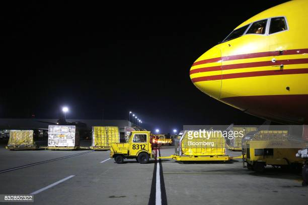 A vehicle moves package containers near a DHL Worldwide Express cargo jet at the company's hub of Cincinnati/Northern Kentucky International Airport...