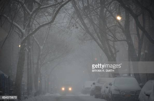 TOPSHOT A vehicle moves through the West Village during a winter storm February 9 2017 in New York / AFP / Bryan R Smith