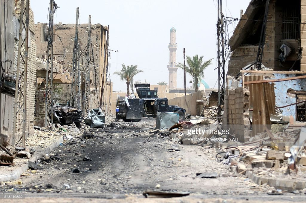A vehicle of the Iraqi police forces is seen in a damaged street in Fallujah on June 28, 2016, after Iraqi forces retook the city from the Islamic State group. Iraqi forces took the Islamic State group's last positions in Fallujah on June 26, 2016, establishing full control over one of the jihadists' most emblematic bastions after a month-long operation. / AFP / HAIDAR