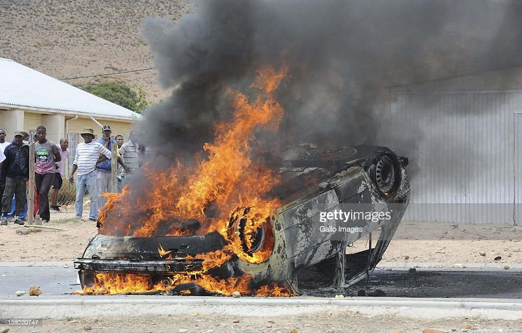 A vehicle on fire at the N1 De Doorns protest on January 9, 2013, in Cape Town, South Africa. Protesting farm workers turned violent as they shut down the N1 by lighting tires on fire and placing large rocks on the road.