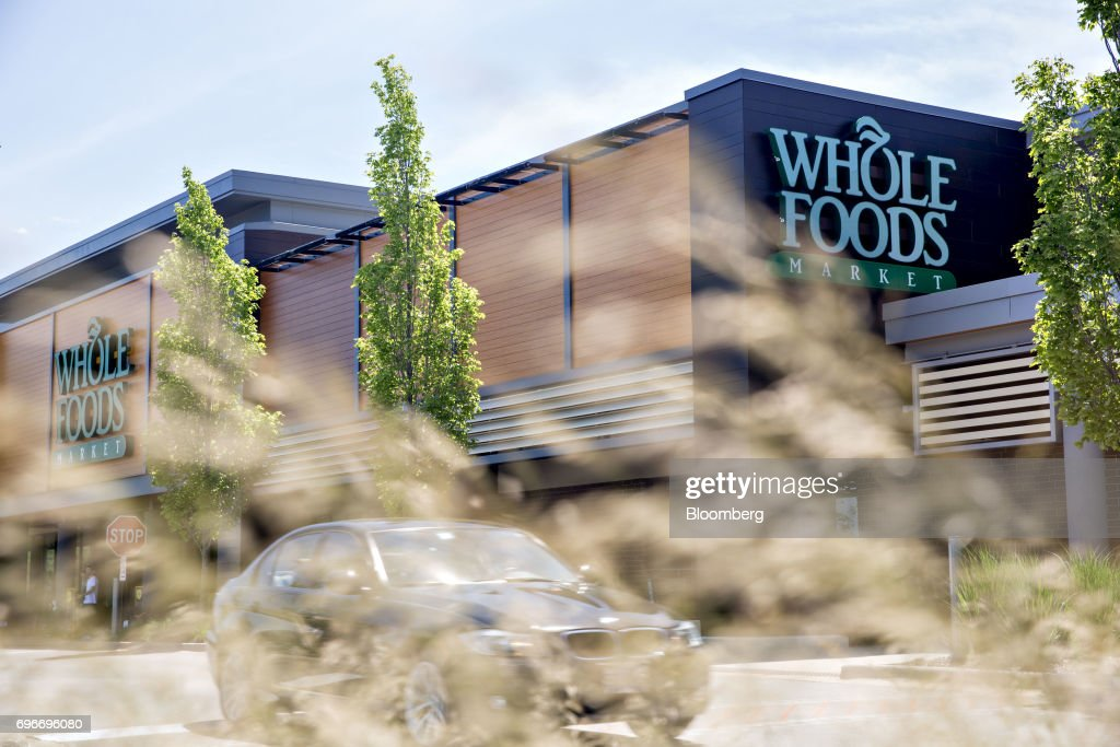 A vehicle passes in front of a Whole Foods Market Inc. location in Willowbrook, Illinois, U.S., on Friday, June 16, 2017. Amazon.com Inc. will acquire Whole Foods Market Inc. for $13.7 billion, a bombshell of a deal that catapults the e-commerce giant into hundreds of physical stores and fulfills a long-held goal of selling more groceries. Photographer: Daniel Acker/Bloomberg via Getty Images