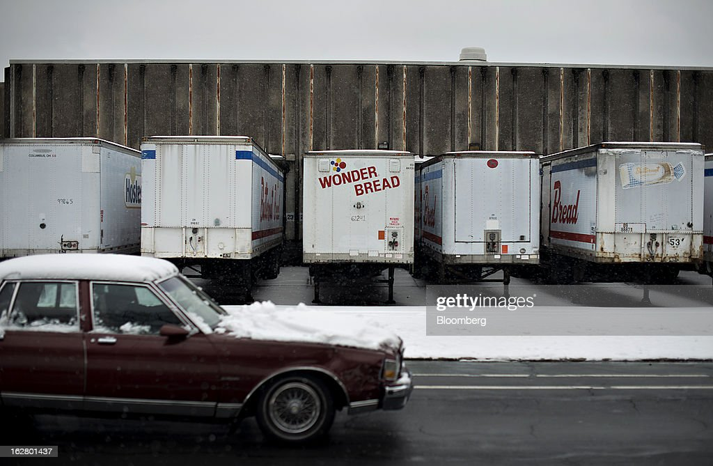 A vehicle passes in front of semi-trailers outside an idled Hostess Brands Inc. bakery in Peoria, Illinois, U.S., on Wednesday, Feb. 27, 2013. Flowers Foods Inc., maker of packaged bakery foods, won the bidding for the majority of the bread-making business of Hostess Brands Inc., including the Wonder, Butternut, Home Pride, Merita and Nature's Pride brands, 20 bread plants, 38 depots and other assets, after no other competing offers were submitted. Photographer: Daniel Acker/Bloomberg via Getty Images